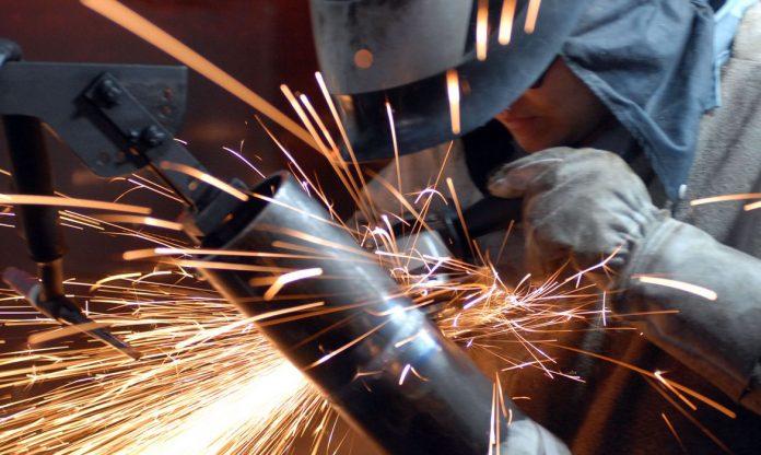 Faíscas laranjas e brancas de solda saem e máquina operada por pessoa paramentada com luvas e protetor frontal de cores cinzas, em ambiente industrial